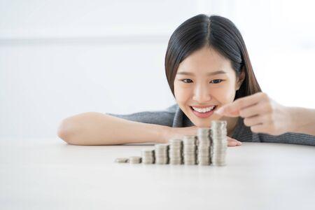 Jonge Aziatische vrouw die stapel muntstukken maakt. investeren sparen financiën concept. Stockfoto