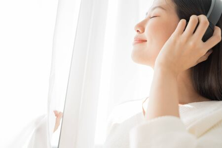 Asian women relax by listening to music using headphones.