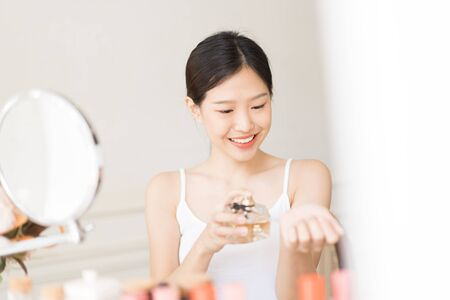 Asian girl with perfume, young woman applying perfume on her wrist and  smelling Stock Photo