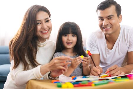 Portrait of happy family daughter girl is learning to use colorful play dough blocks toy together with parent