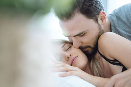 Young couple kissing cheek in the bed wake up in the morning. loving couple in bedroom