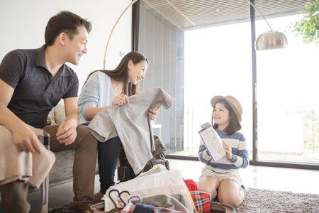 Glückliche asiatische Familie bereitet sich auf Reisen zu Hause vor. Mutter Tochter und Vater packen Koffer für die Reise.