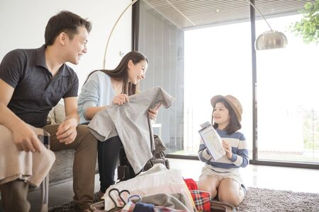 Happy Asian family is preparing for travel at home .Mom daughter and father are packing suitcases for the trip.