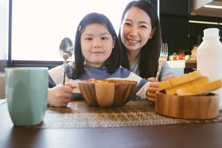mom and daughter eating Cereals with milk having breakfast in kitchen.