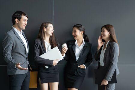 Asiatische Geschäftsleute diskutieren vor dem Bürogebäude. Junger Geschäftsmann und Geschäftsfrau sprechen in der Pause miteinander.
