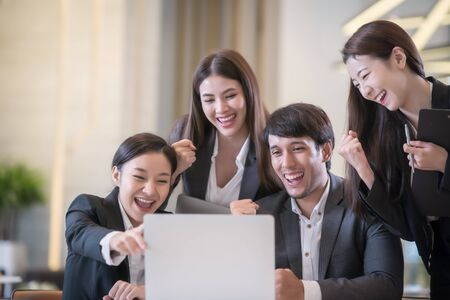Young Asian business people are meeting in office . Group of Business team working Meeting at the screen monitor