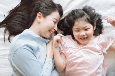 Mutter und ihr Tochtermädchen, das ihre Mutter im Schlafzimmer umarmt. Glückliche asiatische Familie