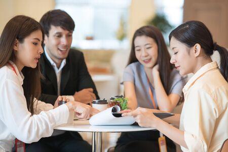Junge Asiatin und Geschäftsleute treffen sich im Büro mit Kollegen. Gruppe von Geschäftsteams, die arbeiten und Ideen über das Projekt mit Partnern teilen Standard-Bild