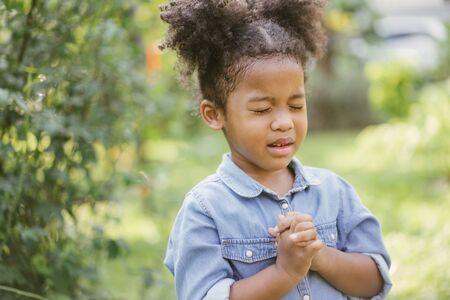 little girl praying. kid prays. Gesture of faith.Hands folded in prayer concept for faith,spirituality and religion Imagens