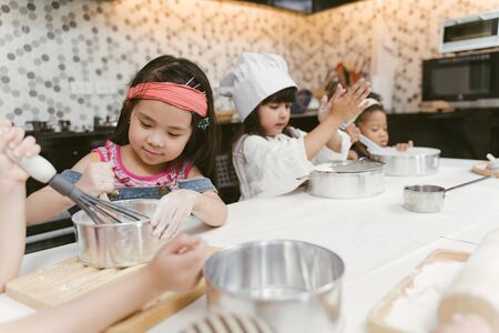 Group of kids are preparing the bakery in the kitchen .Children learning to cooking cookies Stock Photo