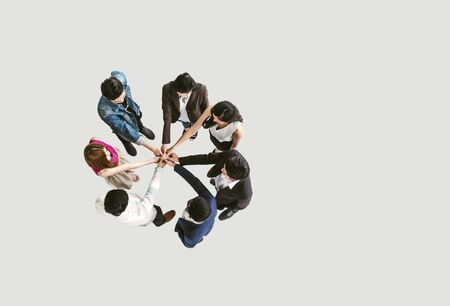 Top view of business people standing with their hands together in a huddle stack hand teamwork assemble together.