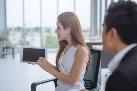 Asian Woman showing discussing present by tablet to colleagues