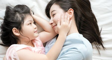 Mother and daughter child girl spending time together in the bedroom Look at each other and smiling .Happy Asian family Stock Photo - 137306905