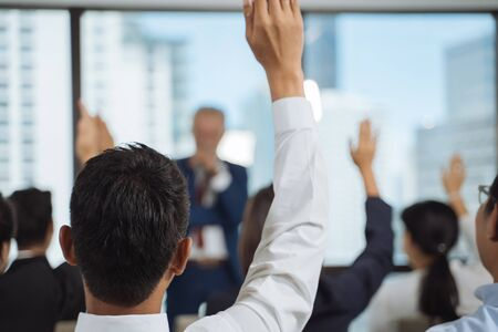 Raised up hands and arms of large group in seminar class room to agree or ask question to speaker at conference seminar meeting room Stock Photo
