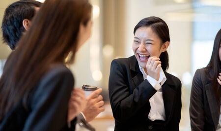 Asiatische Geschäftsleute, die im Bürogebäude sprechen und lachen. Junger Geschäftsmann und Geschäftsfrau sprechen in der Pause miteinander.