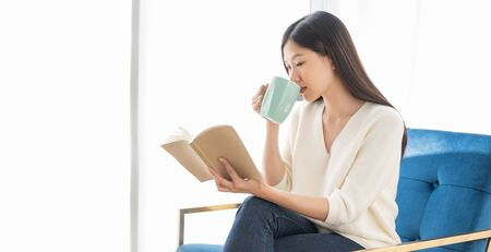 Portrait Asian woman reading book and relaxing with coffee at home
