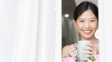 Portrait Asian beauty woman relaxing with coffee at home .Girl and coffee tea in the morning at window.