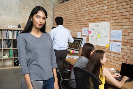 portrait of young Asian business woman holding digital tablet laptop at at creative office workplace. team in meeting in background Reklamní fotografie