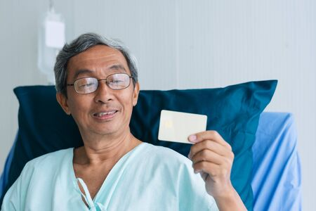 Asian patient elderly man showing credit card on hospital bed in hospital. payment health Insurance medical treatment concept