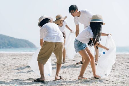 Asian Family volunteer picking up a plastic bottle on a beach with a sea to protect an environment