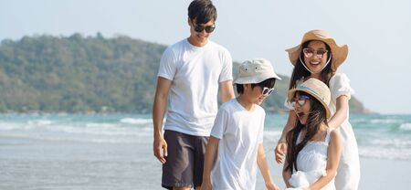 Asian Family walking at beach with kids happy vacation concept