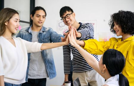 Young Asian creative business team  giving a high fives gesture teamwork togetherness collaboration celebration party success concept