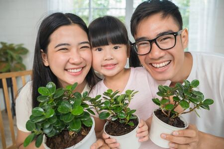 Asian family showing plant flowers for home gardening concept