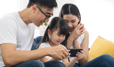 Happy Asian family using phone for playing game or watching movies family and home lifestyle concept Reklamní fotografie