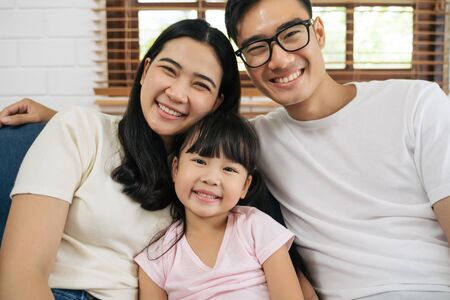 Portrait of happy Asian family spending time together on sofa in living room. family and home concept.