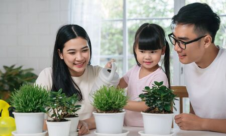 Asian family watering the plants flowers for home gardening concept