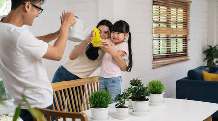 Asian family watering the plants flowers and playing together at home gardening concept Reklamní fotografie