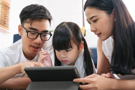 Asian family spending time together in living room. Daughter using tablet learning education technology with family together.