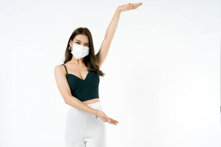 Asian woman wearing hygienic mask to prevent infection corona virus Air pollution pm2.5 showing hand to put text here she wearing a sexy shirt shoot in shot isolated on white background