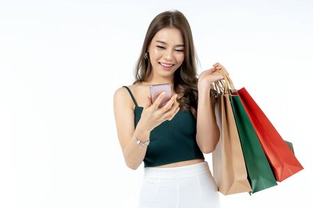 Young Asian woman using smart phone and holding shopping bag shoot in isolate white background. shopping payment concept