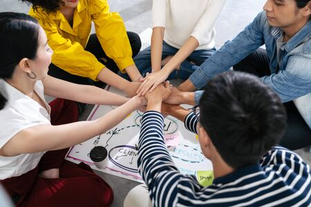 Group of Asian team creative business people join hands partnership teamwork concept