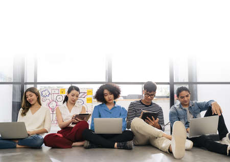 Group of young happy Asian creative business people or hipster student using electronic devices tablet and laptop connection together in modern office. Creative lifestyle young people concept Stok Fotoğraf