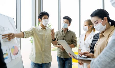 Group of asian business people meeting and working in office and wear mask for protect  prevent infection corona virus covid 19. Reklamní fotografie