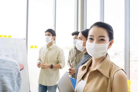 Group of asian business people meeting and working in office and wear mask for protect prevent infection corona virus covid 19. Foto de archivo