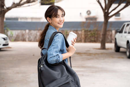 Portrait of young Asian woman student with coffee and backpack Reklamní fotografie