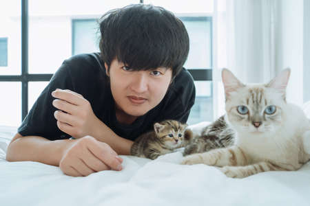 Portrait Young Asian man with family cat on bed at home