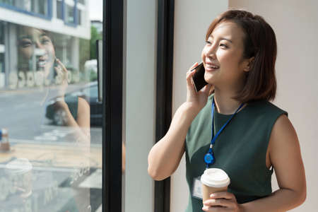 young Asian business woman talking on phone in office and hold coffee cup Reklamní fotografie