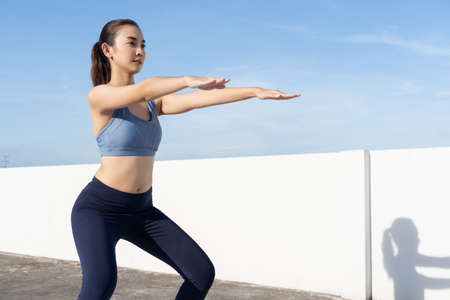 Young beauty Asian woman workout doing squats outdoor rooftop.Fitness practice training health care concept