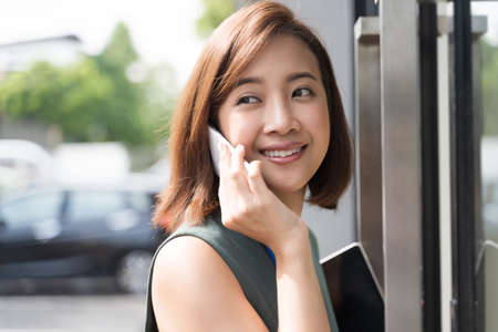 Close up Portrait of beauty young Asian business woman talking on the phone outside of office