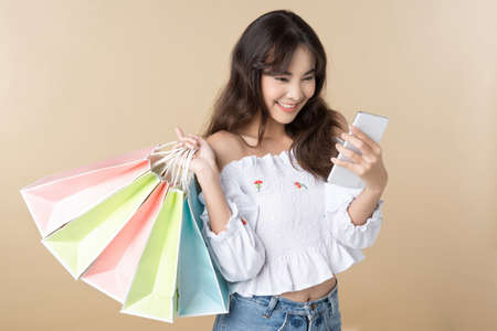 Young Asian woman holding shopping bag using phone on isolate background Reklamní fotografie