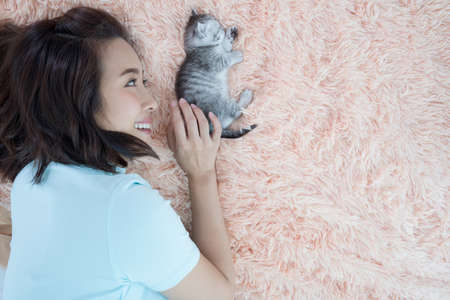 Young Asian woman with kitten cat pet sleep on the bed