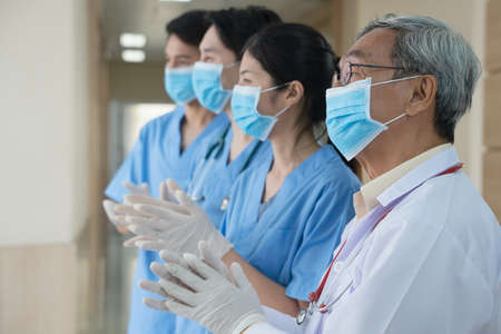Nurse and Doctor health workers team applauding clapping their hands in gratitude for congratulating