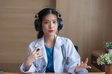 Asian Female doctor wear headphones working at office desk and smiling at camera, video call consultation, patient and doctor talk concept.