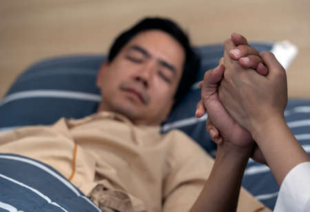 Holding the hand asian man patient in hospital