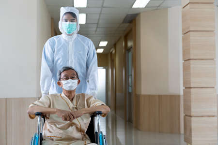 Doctor in hazmat protection suit pushing coronavirus asian mature patient on wheelchair in hospital