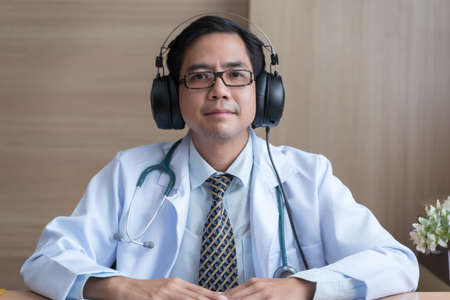 Asian man doctor wear headphones working at office desk and smiling at camera, video call consultation, patient and doctor talk concept.